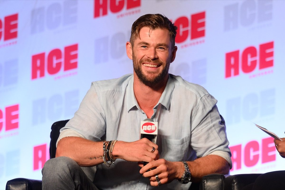 chris hemsworth sitting down and smiling