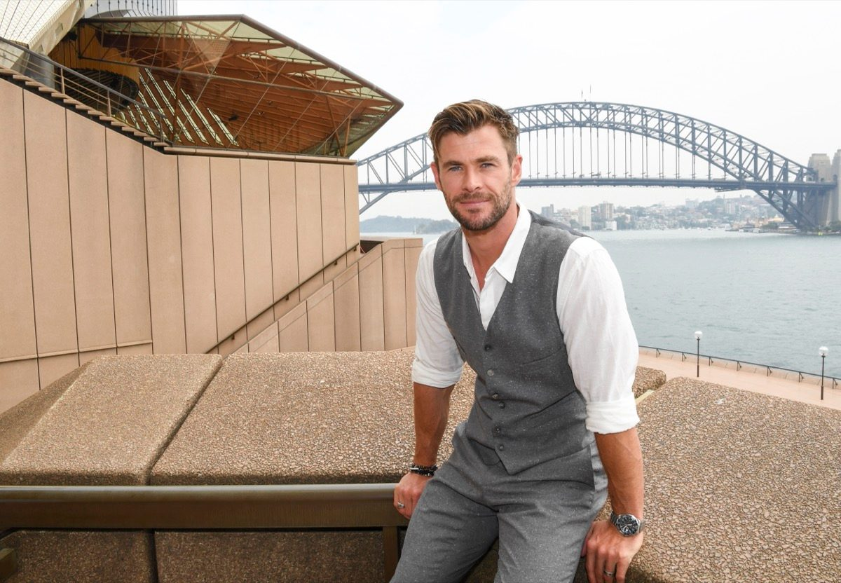 chris hemsworth sitting outside in gray suit