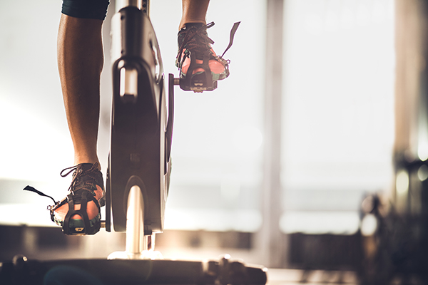 Cropped shot of person's feet on indoor bike pedals