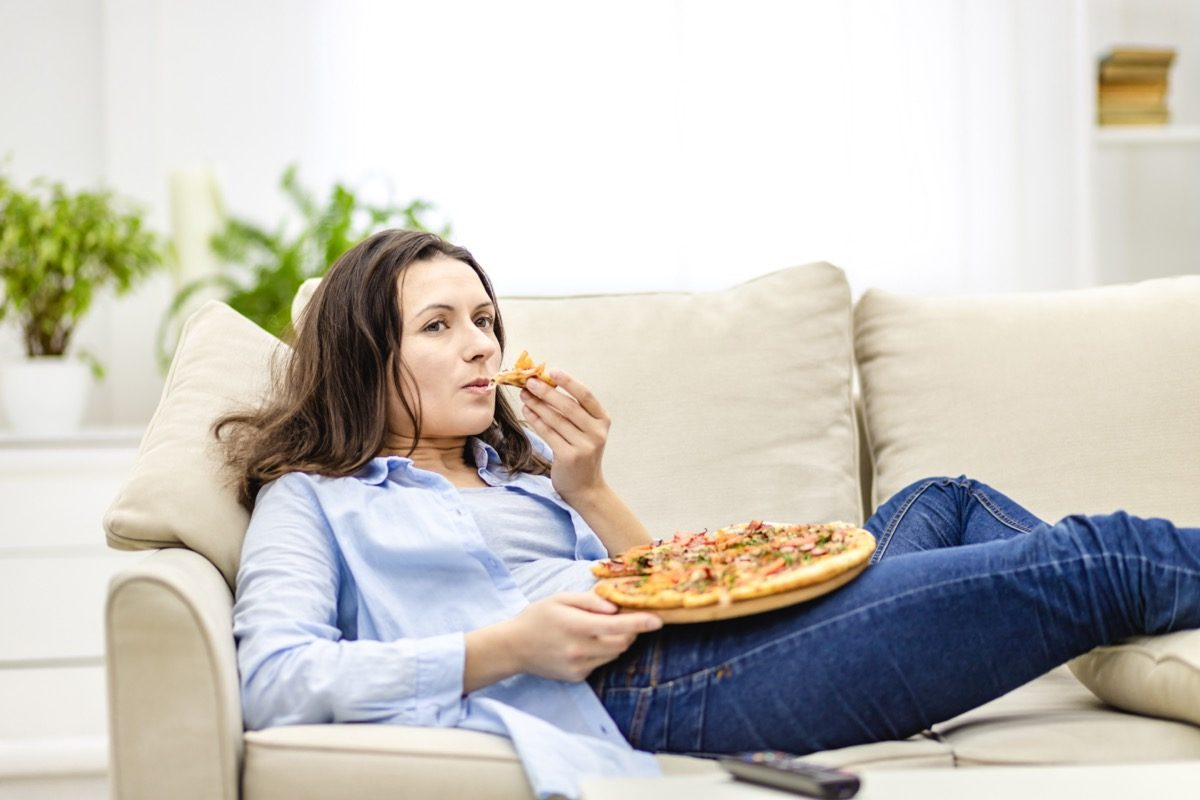 woman is chewing pizza, while laying on the white sofa. She is watching TV shows, being on blurred background.