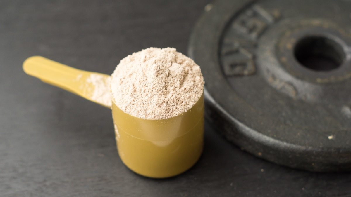 whey protein powder in yellow scoop next to weight plate