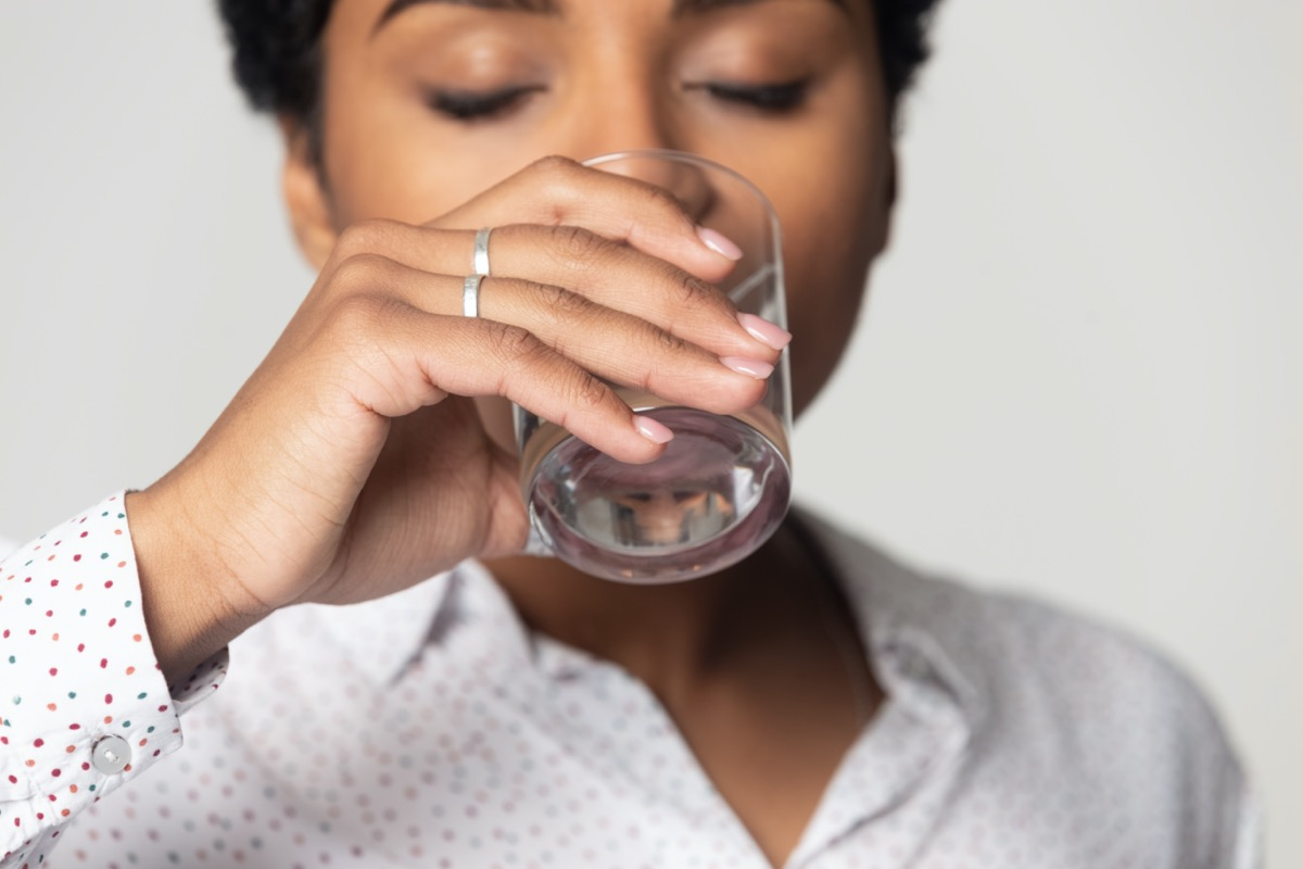 with closed eyes drinking clean mineral water close up, young woman holding glass