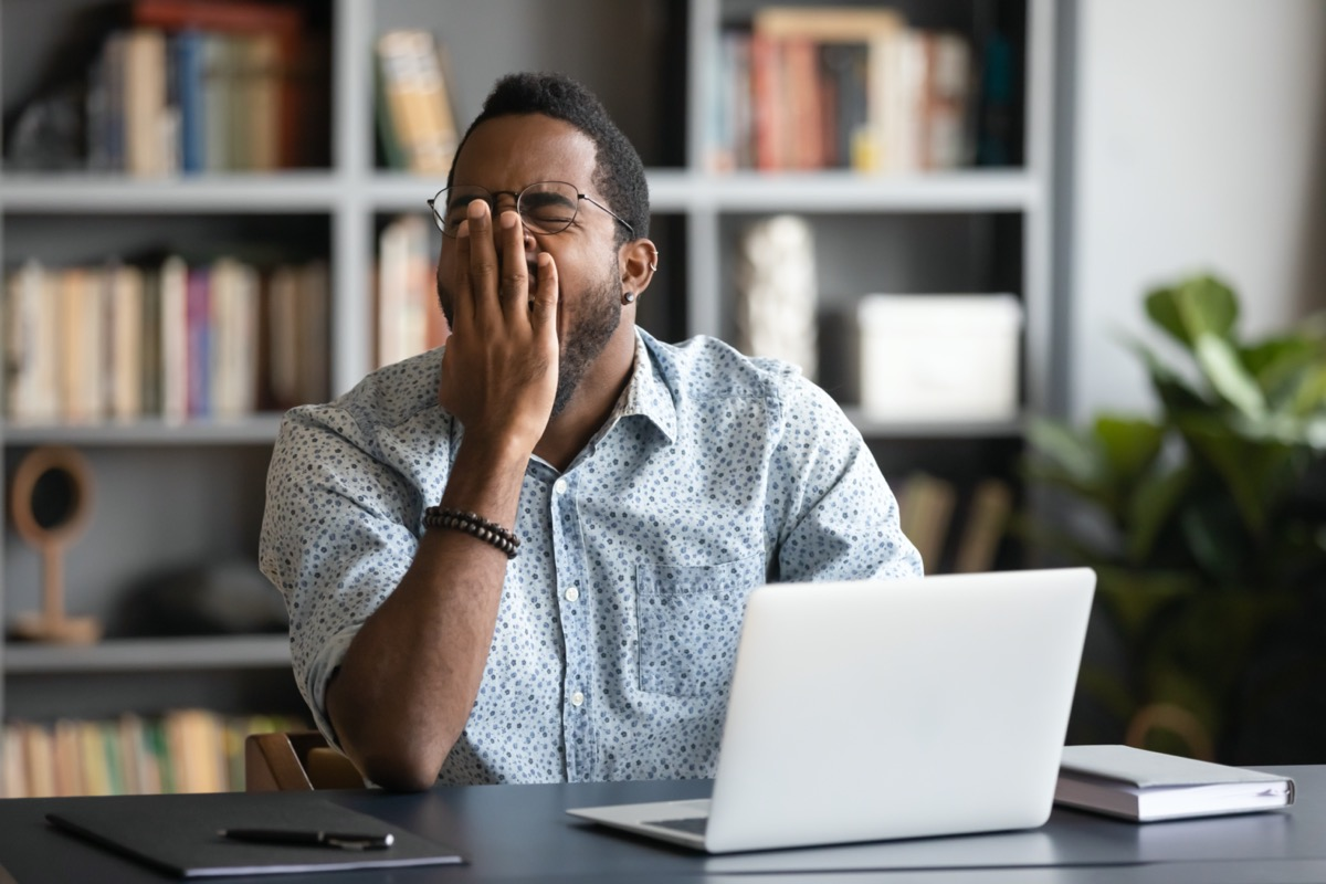 Tired african American male worker or student sit at desk sigh yawn feeling stressed or fatigue overwork in office
