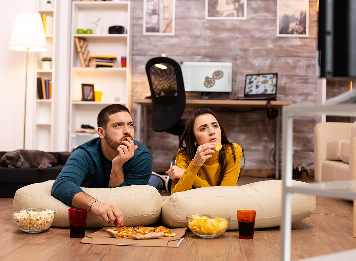 couple watching tv snacking