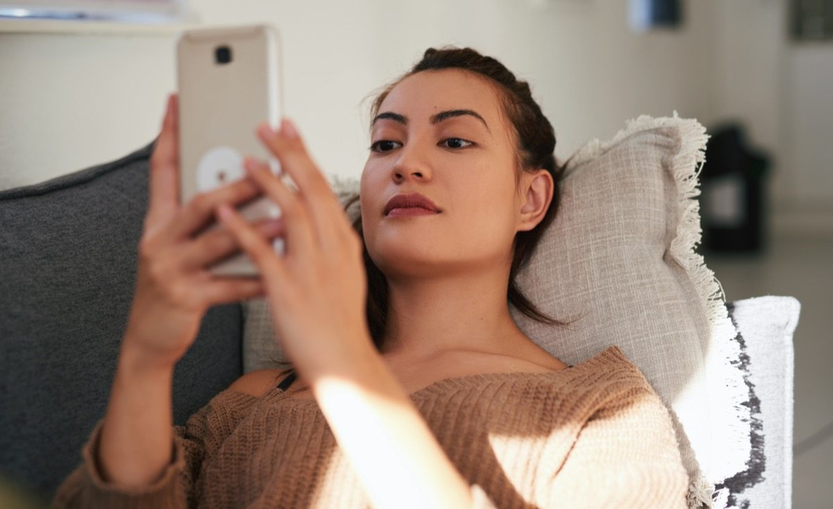 woman using a smartphone on the sofa at home