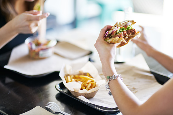 Woman eating a burger and fries