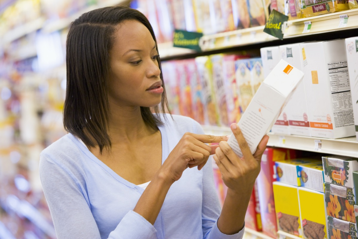 Female shopper checking food labelling in supermarket
