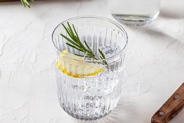 Glass of seltzer water with rosemary and lemon