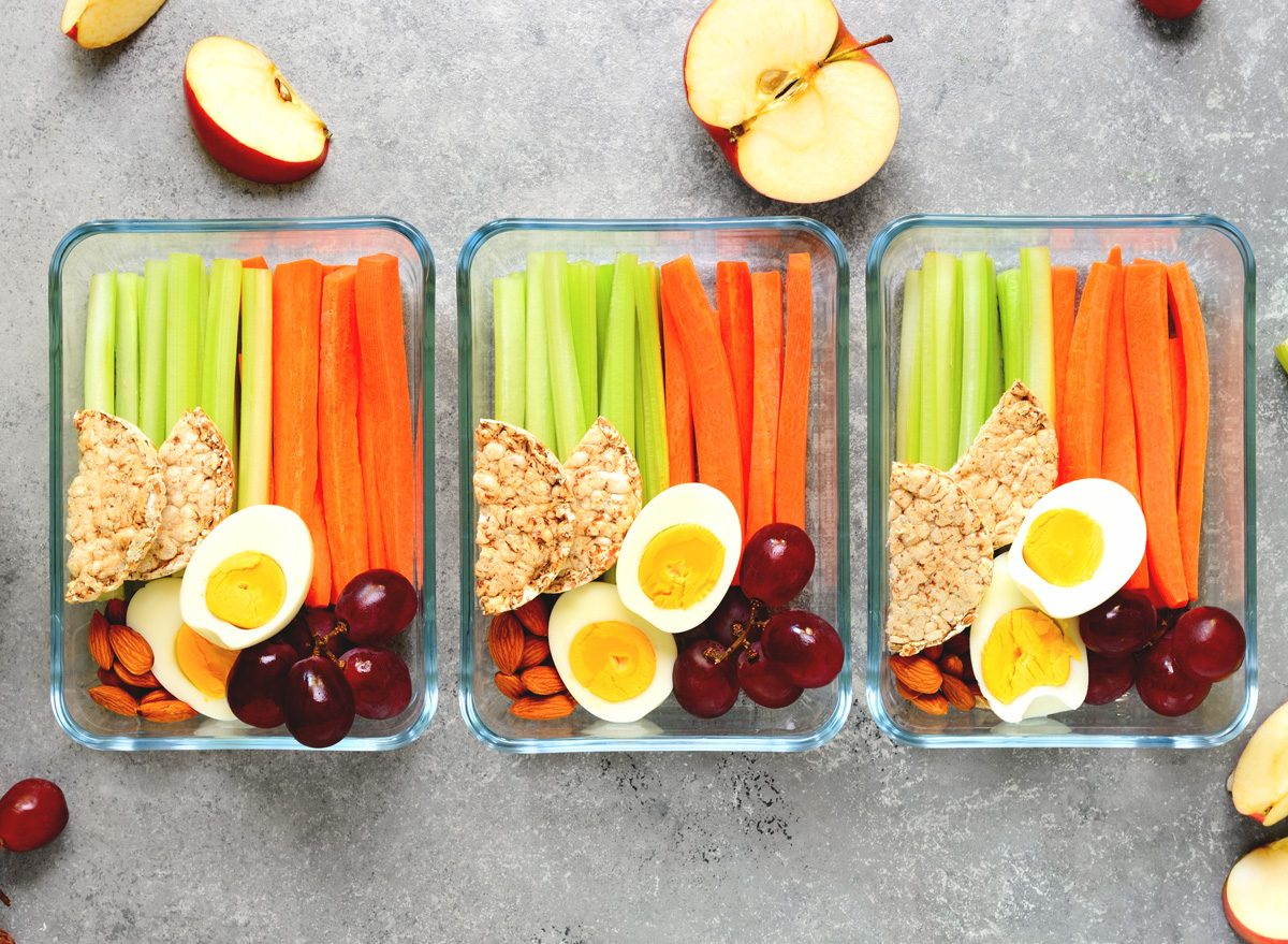 Healthy snack meal prep with cut carrots celery hard boiled eggs apples grape almonds and rice cakes