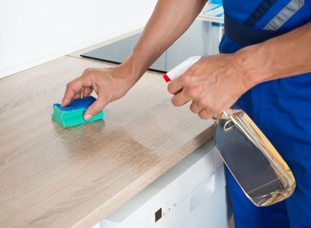Man cleaning kitchen with a sponge