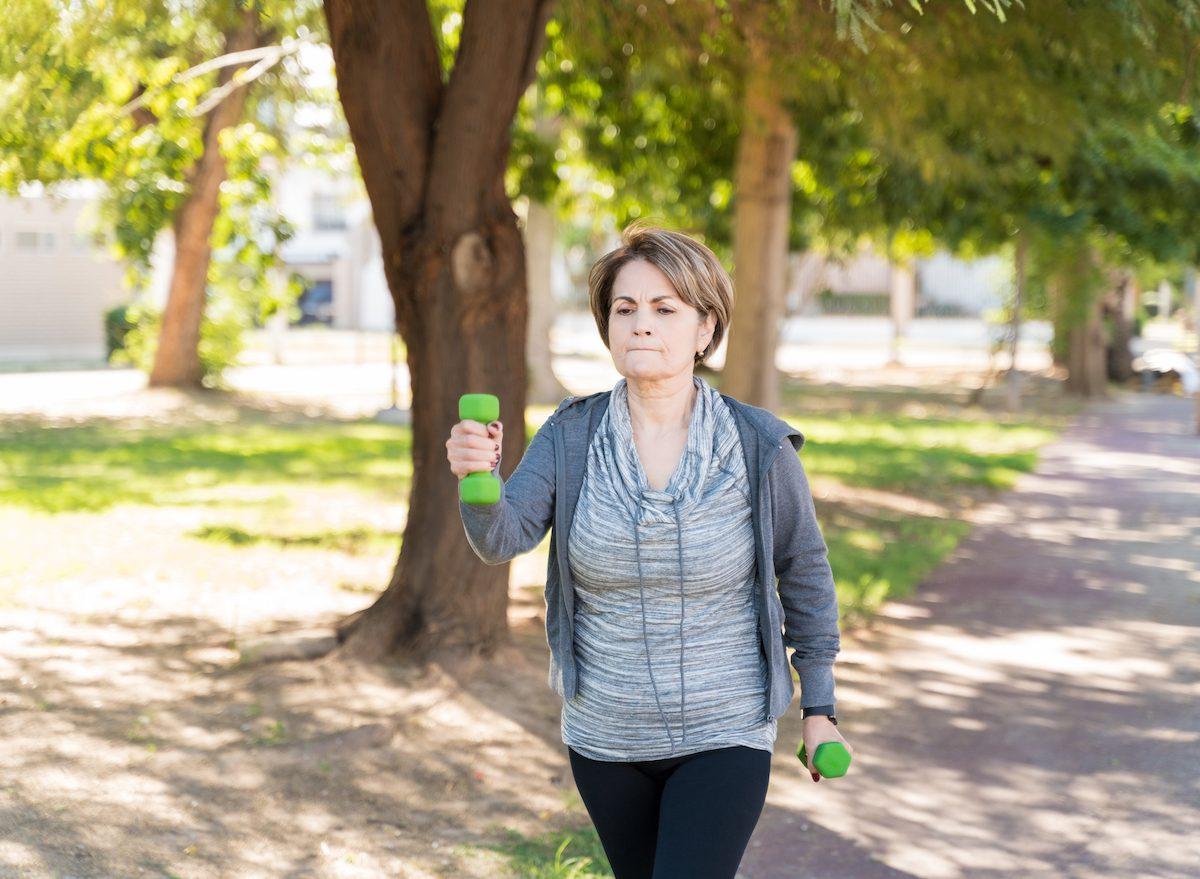 older woman walking with hand weights